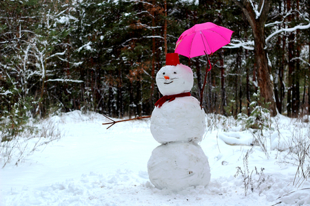 Snowman with pink umbrella standing in winter landscape, outdoor winter concept Stock Photo