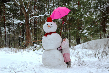 A little child girl has a look at snowman with pink umbrella standing in winter landscape, winter concept, family spending time outdoors