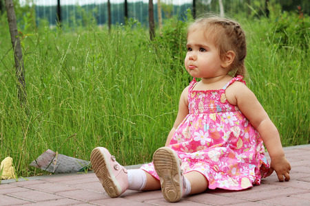 sitting on the ground: The offended little girl with pouting lips sitting on the ground, summer outdoor Stock Photo