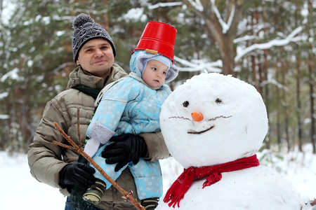 Happy father with little toddler boy in warm overalls standing near a snowman in winter landscape, winter concept, family spending time outdoors Stock Photo