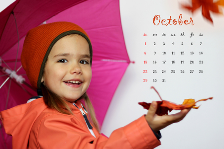 clothes organizer: October 2017 calendar with cute little girl child in orange coat with pink umbrella and yellow maple leaves over white background
