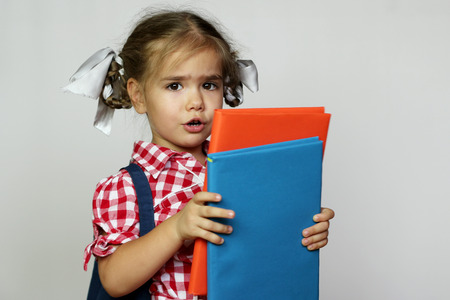 writing implements: Portrait of cute smiling girl with backpack and colorful books, education and back to school concept