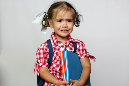 Portrait of cute crying girl with backpack and colorful books, education and back to school concept