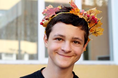Happy teenager in maple wreath, autumn apollo, fall outdoor portrait