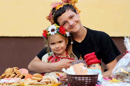 Cute Ukrainian small girl wearing national costume and happy teenager in maple wreath before a table full of different cakes and sweets, autumn harvest and trade fair