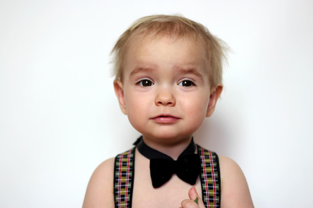 Little boy in suspenders and black bow-tie looking confusedly with funny face, isolated portrait over white background, romantic and love concept Banque d'images