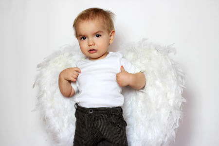 angel alone: Beautiful blond toddler in a white t-shirt with white wings as a Cupid over white background, Saint Valentines Day card, romantic and love concept