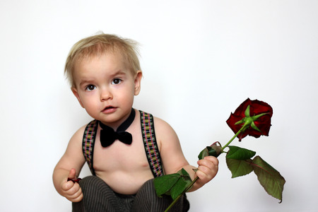 enthusiasm: Little boy in suspenders and black bow-tie squatted and holding a red rose, looking interested and with enthusiasm, isolated portrait over white background, romantic and love concept
