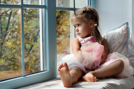 Sad little girl sitting alone at home near the window and looking on the autumn street, indoor portrait, childhood and family concept