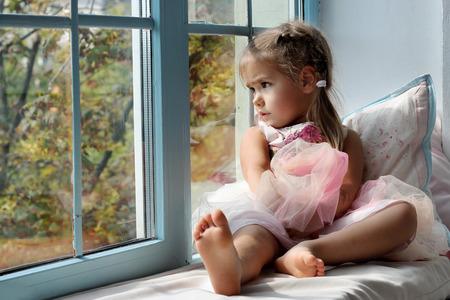 Trauriges kleines Mädchen alleine zu Hause am Fenster sitzt und schaut auf den Herbst Straße, Innen-Porträt, Kindheit und Familienkonzept Standard-Bild