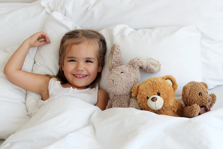 awake: Top view of cute awaking girl with her toy animals, happy family concept, indoor horizontal portrait