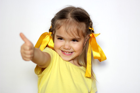 Cute little girl with yellow bows and yellow T-shirt showing thumb up gesture over white background, sign and gesture concept Stock Photo