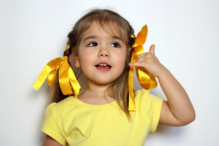 Cute little girl with yellow bows and yellow T-shirt making call me sign with her hand over white background, sign and gesture concept
