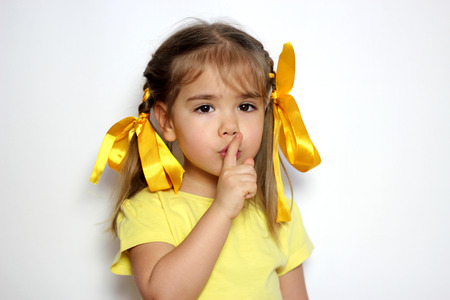 Cute little girl with yellow bows and yellow T-shirt doing silence sign the finger near lips over white background, sign and gesture concept Stock Photo