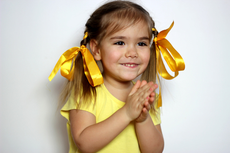Cute little girl with yellow bows and yellow T-shirt claps her hands over white background, sign and gesture concept