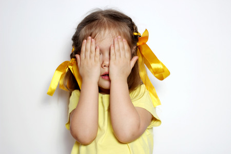 Cute little girl with yellow bows and yellow T-shirt covered her eyes with her hands like during peek-a-boo game, over white background, sign and gesture concept Imagens
