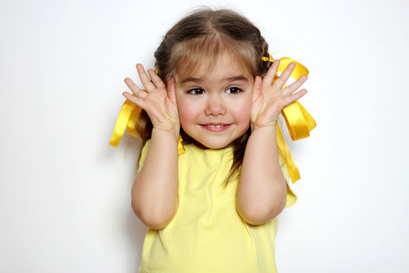 Cute little girl with yellow bows and yellow T-shirt covered her eyes with her hands like during peek-a-boo game, over white background, sign and gesture concept Banque d'images