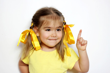 Cute little girl with yellow bows and yellow T-shirt raising finger in funny attention gesture over white background, sign and gesture concept