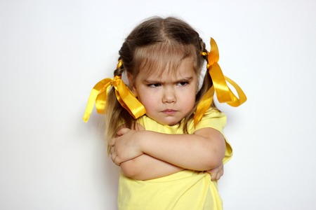 Angry little girl with yellow bows and yellow T-shirt over white background, sign and gesture concept Archivio Fotografico