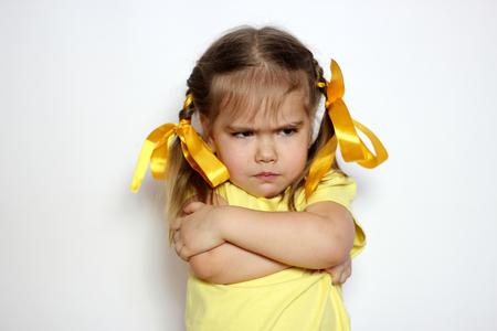 Gniewna mała dziewczynka z żółtymi łękami i żółtą koszulką nad białym tła, znaka i gesta pojęciem ,.