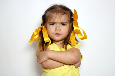 Angry little girl with yellow bows and yellow T-shirt over white background, sign and gesture concept Banque d'images
