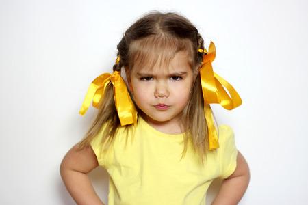 Boos meisje met gele bogen en gele T-shirt over een witte achtergrond, te ondertekenen en gebaar-concept