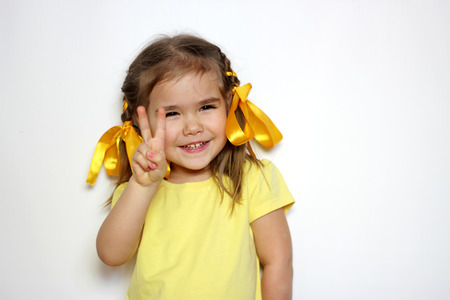Cute little girl with yellow bows and yellow T-shirt shows victory gesture over white background, sign and gesture concept