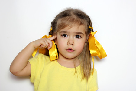 Cute little girl with yellow bows and yellow T-shirt making a crazy gesture over white background, sign and gesture concept