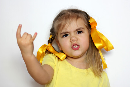 Cute little girl with yellow bows and yellow T-shirt shows horns (love hard rock) gesture over white background, sign and gesture concept Banque d'images