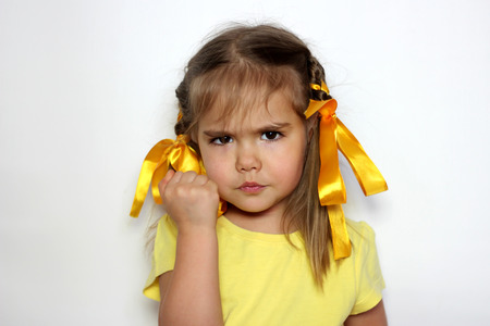 Angry little girl with yellow bows and yellow T-shirt raising his fist over white background, sign and gesture concept