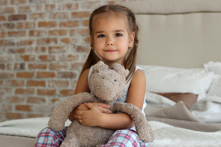 gentle dream vacation: Cute little girl in pajama hugging her toy hare on the bed at home, happy childhood concept, indoor horizontal portrait Stock Photo