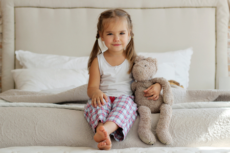 fond of children: Cute little girl in pajama hugging her toy hare on the bed at home, happy childhood concept, indoor horizontal portrait Stock Photo