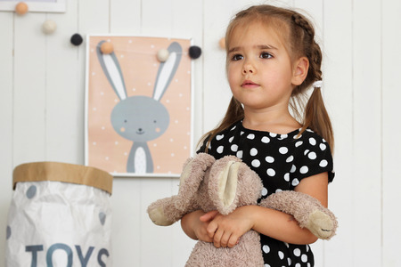 Dreaming girl standing in the nursery near the picture with bunny on the wall and holding toy hare in the hand, childhood and family concept, horizontal indoor portrait