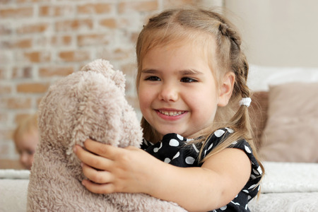 attachment: Close-up of cute little girl in black and white dress hugging her toy hare, happy childhood concept, indoor horizontal portrait