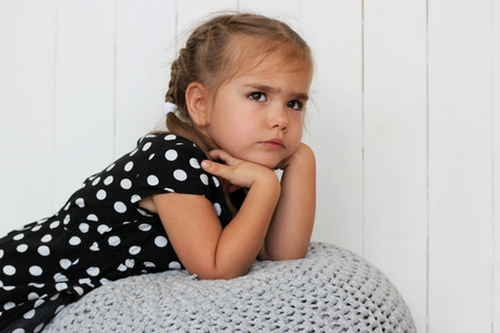 Close-up of cute little girl in black and white dress leaning her elbows on padded stool, child emotions concept, indoor portrait