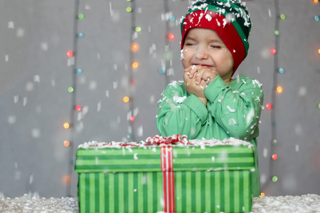 Portrait of happy toddler boy in a green hat like a little elf with gift box on the snow over white Christmas background, winter holiday concept, happy family and childhood