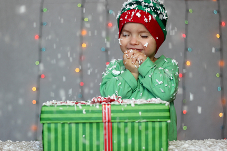 Portrait of toddler boy with closed eyes in a green hat like a little elf dreaming before a gift box on the snow over Christmas background, winter holiday concept, happy family and childhood Stock fotó