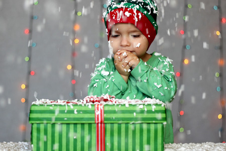 Portrait of toddler boy in a green hat like a little elf looking at the gift box on the snow over Christmas background, winter holiday concept, happy family and childhood