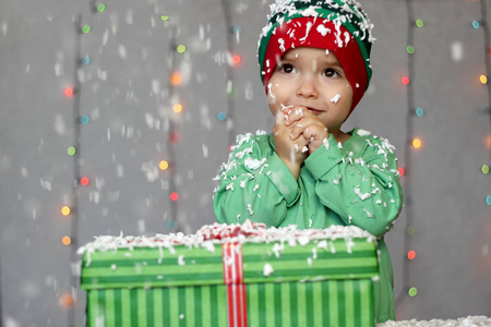 Portrait of toddler boy in a green hat like a little elf dreaming near the gift box on the snow over Christmas background, winter holiday concept, happy family and childhood