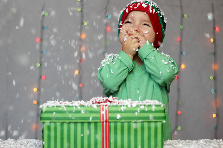 rapturous: Portrait of toddler boy in a green hat like a little elf dreaming near the gift box on the snow over Christmas background, winter holiday concept, happy family and childhood