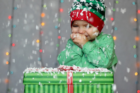 rapturous: Portrait of happy toddler boy in a green hat like a little elf with gift box on the snow over white Christmas background, winter holiday concept, happy family and childhood