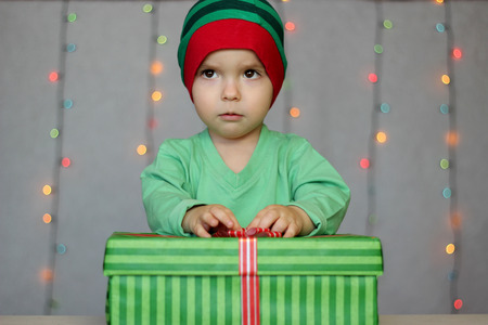Portrait of happy little boy opening gift in the box over Christmas background, winter holiday family concept