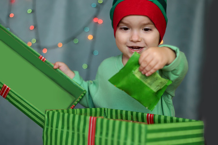 Portrait of happy little boy like elf opening a box with gift over Christmas background, winter holiday family concept