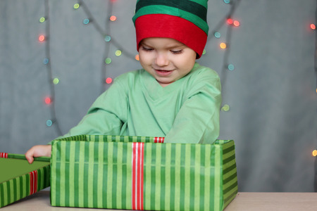 Portrait of happy little boy like elf reaching a gift from the box over Christmas background, winter holiday family concept