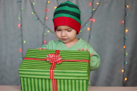 rapturous: Portrait of happy little boy like elf opening a box with gift over Christmas background, winter holiday family concept