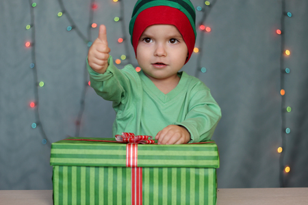 Portrait of happy little boy like elf showing a thumb and sitting near a box with gift over Christmas background, winter holiday family concept Stock fotó
