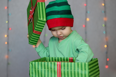 rapturous: Portrait of happy little boy like elf reaching a gift from the box over Christmas background, winter holiday family concept