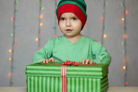 Portrait of happy little boy like elf waiting to open a box with gift over Christmas background, winter holiday family concept Stock fotó