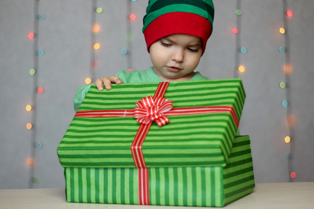 Portrait of happy little boy like elf glancing at a gift in the box over Christmas background, winter holiday family concept