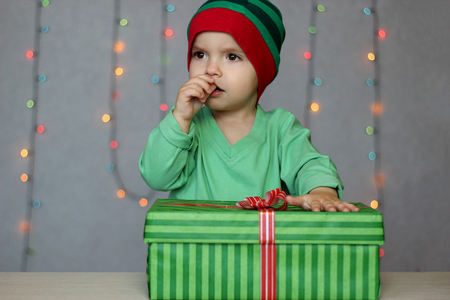 Portrait of happy little boy like elf trying to guess what a gift in the box over Christmas background, winter holiday family concept